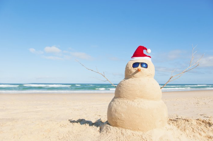 A photo of a snowman made out of sand on a beach, with blue skies overhead. The Snowman is wearing a red hat and sunglasses.