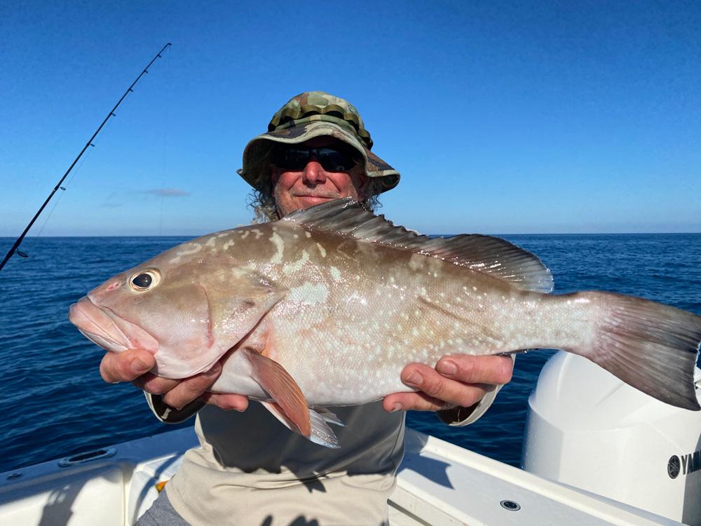 Mans friend holding redfish he caught